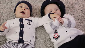 Two little boys in suits of sailors hold each other`s hands lying on the floor. stock video