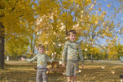 Two little boys throw colorful leaves in air Stock Photo