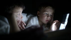 Two little boys try to watch the film at night. Two little boys in bed try to watch the film at night using the tablet stock video footage