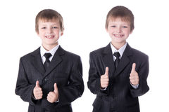 Two little boys twins in business suits thumbs up isolated on wh Royalty Free Stock Image
