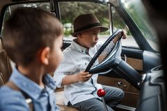 Two little boys in vintage clothes are sitting in a retro car.  royalty free stock images