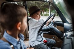 Two little boys in vintage clothes are sitting in a retro car.  stock photo