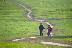 Two little boys walking together on the path Stock Image
