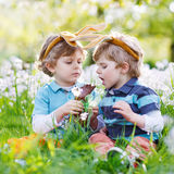 Two little boys wearing Easter bunny ears and eating chocolate royalty free stock photo
