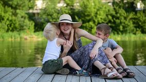 Two little boys whisper something in their mom`s ear. Summer day. Pier on the river bank. Happy family.  stock video