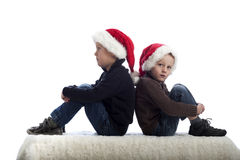 Two little boys with xmas hats Royalty Free Stock Photography