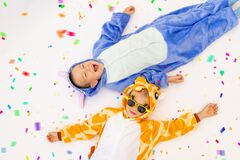 Two little brother boys in bright costumes on a white isolated background with confetti, children`s birthday, place for text