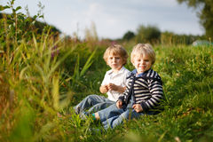 Two little brother boys playing near forest lake on summer eveni Royalty Free Stock Image
