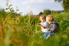 Two little brother boys playing near forest lake on summer evening. Cute siblings playing together. Two little brother boys playing near forest lake on summer royalty free stock photo