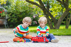 Two little brother boys playing with red school bus Stock Photo