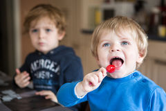 Two little brother boys watching tv indoor Stock Photo