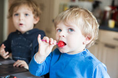 Two little brother boys watching tv indoor. Two little brother boys watching tv and eating candy indoor Stock Photo