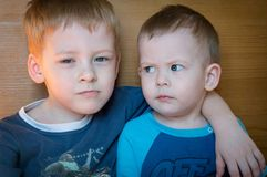 Two little brother sitting in each other`s arms stock photos