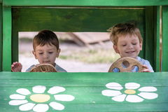 Two little brother toddlers playing with toy car in summer garden. Boys having fun and good time. In wooden at playground royalty free stock image
