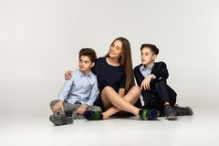 Two little brothers with beautiful sister in black dress royalty free stock photography