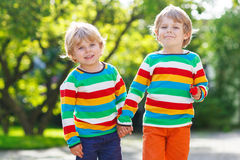 Two little brothers children in colorful clothing walking hand i Stock Image