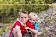 Two little brothers hugging at the lake or river on warm sunny day. Two little brothers playing and hugging at the lake or river on warm sunny day. Active royalty free stock images