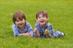 Free Two Little Brothers Laying In Grass Stock Images - 62208454