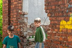 Two little brothers are orphans, living in an abandoned and abandoned house, children of war. Staged photo royalty free stock photography