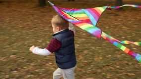 Two little brothers play with a kite in the autumn city park. Slow motion. stock video