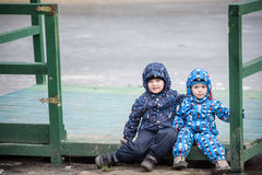 Two little brothers playing, on autumn landscape, sitting and smiling  the wooden pier near frozen lake Royalty Free Stock Photos