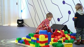 Two little brothers playing with constructor. NOVOSIBIRSK - MARCH 20: Two little brothers playing with constructor. Children building wall from blocks on stock footage