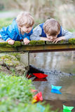 Two little brothers playing with paper boats by a river Stock Photos
