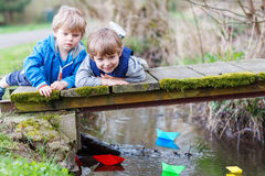 Two little brothers playing with paper boats by a river Stock Image