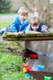 Two little brothers playing with paper boats by a river Stock Images