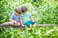 Two little brothers playing with paper boats by a river on warm and sunny summer day. Royalty Free Stock Photography