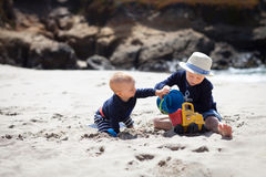 Two little brothers playing togther on the beach Stock Photos