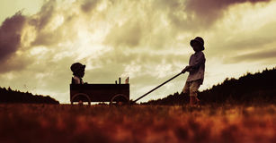 Two little brothers playing with the wooden carriage Stock Photos
