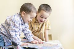 Two little brothers read a children`s book. Children`s friendship, fun education royalty free stock image