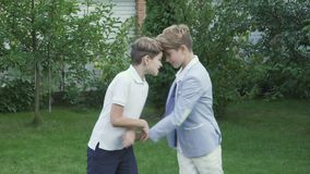 Two little brothers shakes hands after fighting. Two little brothers fights in the garden. The children plays outdoors at the backyard of country house. The boys stock footage