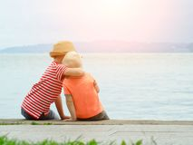 Two little brothers sit on a pier and embrace against the sea an Stock Photos