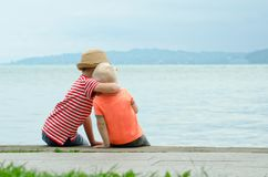 Two little brothers sit on a pier and embrace against the sea and mountains in the distance. Back view.  Stock Photography