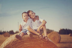 Two little brothers sitting on a haystack in wheat Stock Image