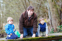 Two little brothers and their dad playing with paper boats by a Royalty Free Stock Image