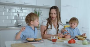 Two little brothers with their mother in a dress are cooking together in a white kitchen burgers laugh and smile stock footage
