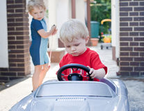 Two little brothers toddlers playing with big toy car. In summer garden stock image