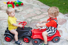 Two little brothers toddlers playing with cars. Two little brother toddlers playing with toy car in summer garden stock image