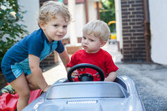 Two little brothers toddlers playing with cars. Two little brother toddlers playing with toy car in summer garden royalty free stock photography