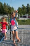 Two little Caucasian blonde girl standing on the dock with fishing rod and show caught fish royalty free stock image