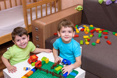 Two little caucasian friends playing with lots of colorful plastic blocks indoor. Active kid boys, siblings having fun building an Royalty Free Stock Images