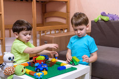 Two little caucasian friends playing with lots of colorful plastic blocks indoor. Active kid boys, siblings having fun building an Royalty Free Stock Photo