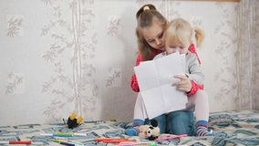 Two little caucasian girl sitting on the bed and drawing royalty free stock photos