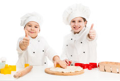 Two little chefs cutting dough with thumbs up Stock Photo