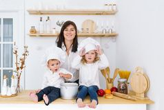 Two little chefs sittting on table in the kitchen with mother stock photo