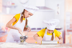 Two little chefs stretch the dough. Two happy young chefs stretch the dough royalty free stock photos