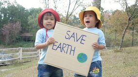 Two little child girl siblings holding `Save the planet` Poster showing a sign protesting against plastic pollution in the forest.